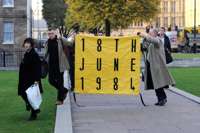 Campaigners from the Orgreave Truth and Justice Campaign carry a banner as they arrive on College Green, London. (PA)
