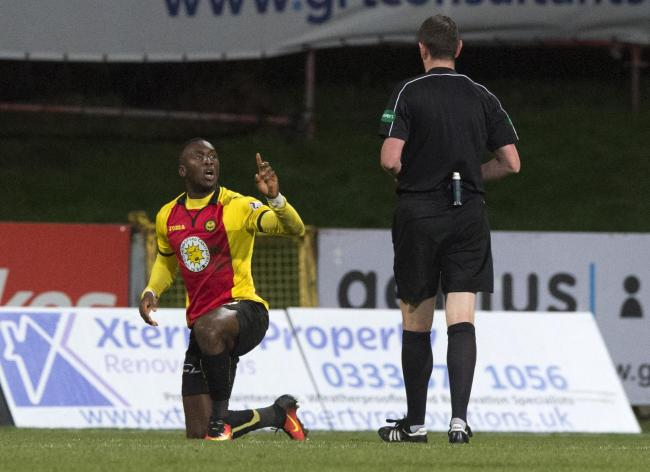 Partick Thistle's Ade Azeez (left) is booked by referee Craig Thomson.
