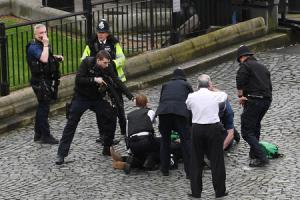 A policeman points a gun at a man on the floor as emergency services attend the scene outside the Palace of Westminster, London,