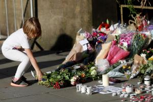 FOR THE INNOCENTS: A girl leaves flowers for the victims of the Manchester Arena suicide bombing that left 22 people dead, including an eight-year-old girl, and 59 injured. Picture: Peter Nicholls
