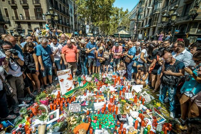 People gather at a makeshift memorial on the Joan Miro mosaic in Las Ramblas, the site where a van came to a halt after it tore through the crowds. Picture: Matthias Oesterle/Alamy Live News