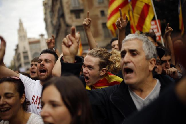 Protestors shout as they gather in front of the Spanish police station in downtown Barcelona, Spain, Tuesday Oct. 3, 2017.