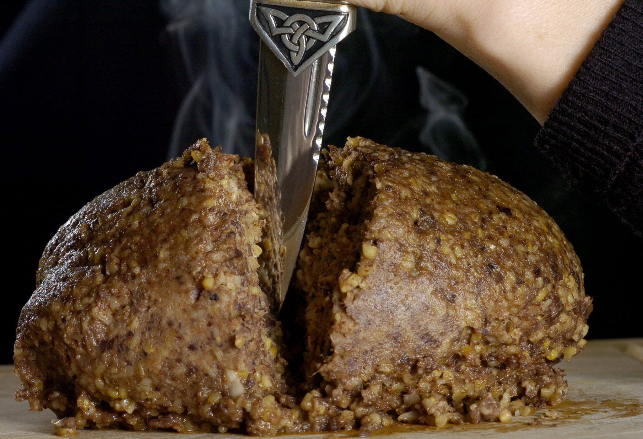 Photograph of a Haggis being cut open witha Skean Dhu..