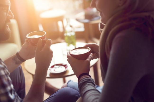 Young couple in love sitting in a cafe, drinking coffee, having a conversation and enjoying the time spent with each other. Selective focus; Shutterstock ID 584406415; Purchase Order: 110218; Job: news; Client/Licensee: sunday herald; Other:.