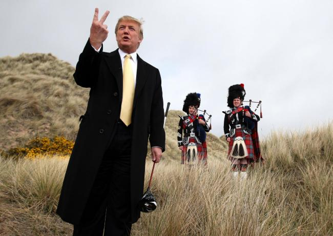Donald Trump humorously gives a two fingered gesture to the media on the Menie Estate, where his controversial luxury golf resort will be built. The coastal resort in Balmedie, Aberdeenshire, will have two golf courses, a 450-bedroom hotel, 950 holiday ap