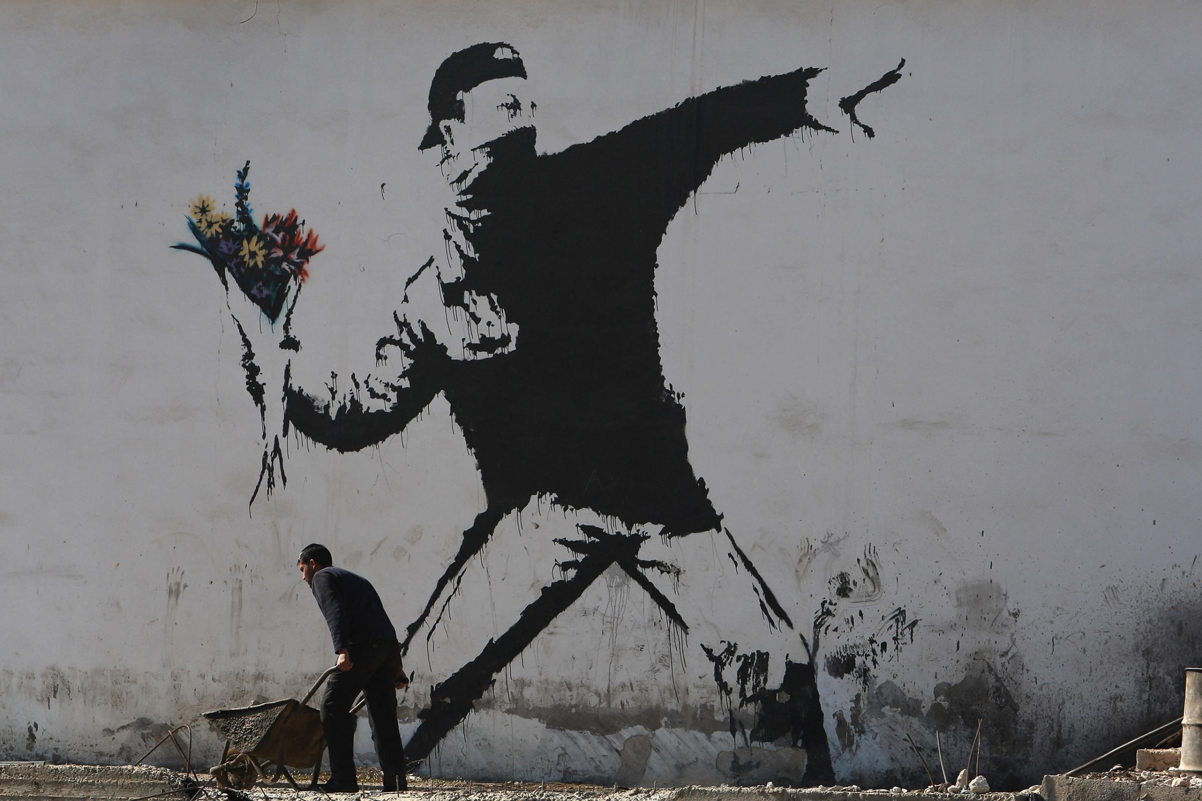 BETHLEHEM, WEST BANK - DECEMBER 05:  A Palestinian labourer works under a large wall painting by elusive British graffiti artist Banksy December 5, 2007 on a building wall in the biblical city of Bethlehem in the West Bank. The Bristol-born artist has ado