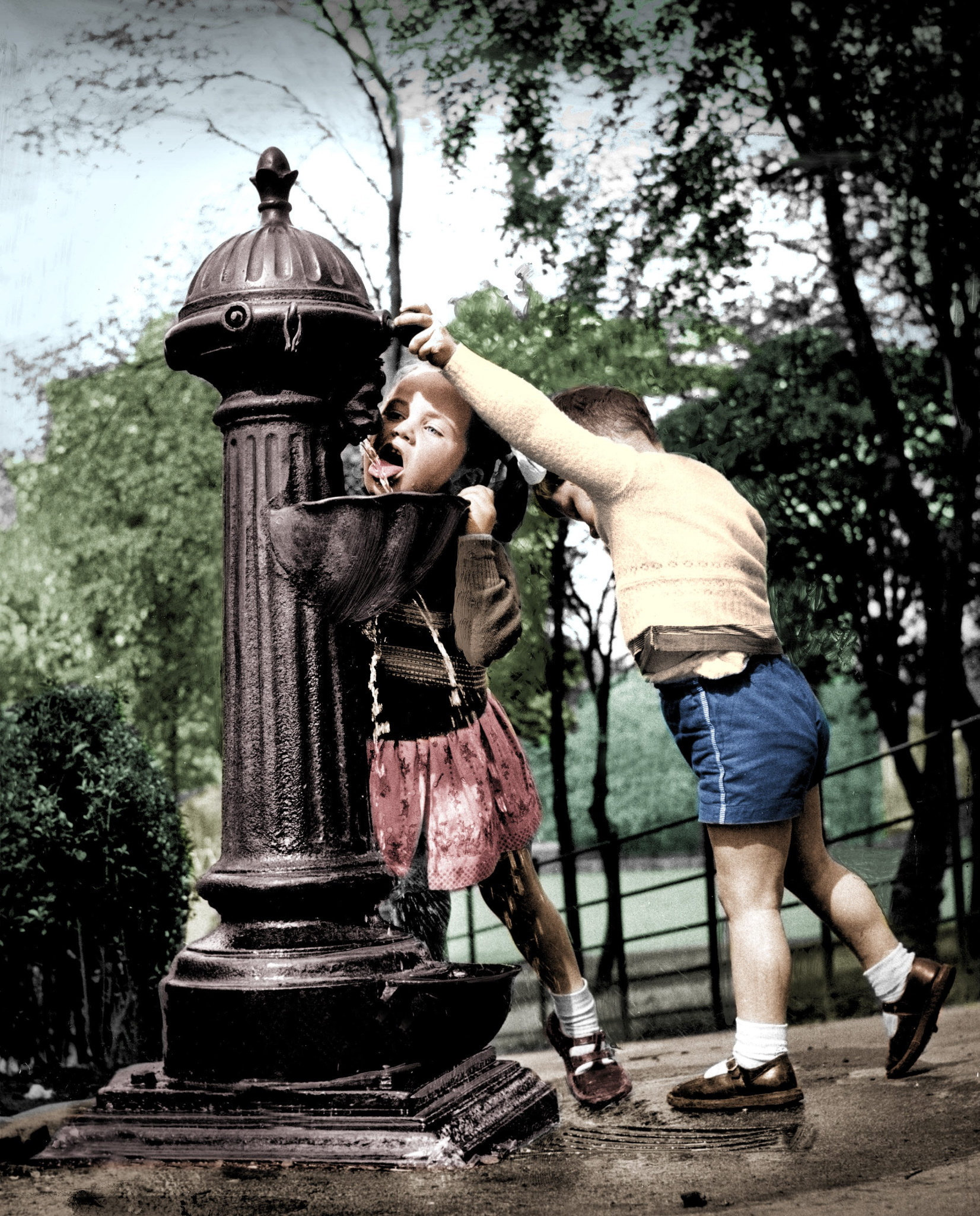 Glasgow: Parks And Open Spaces..A three year old boy turning on the water for his sister at the drinking fountain in Queen's Park, Glasgow..