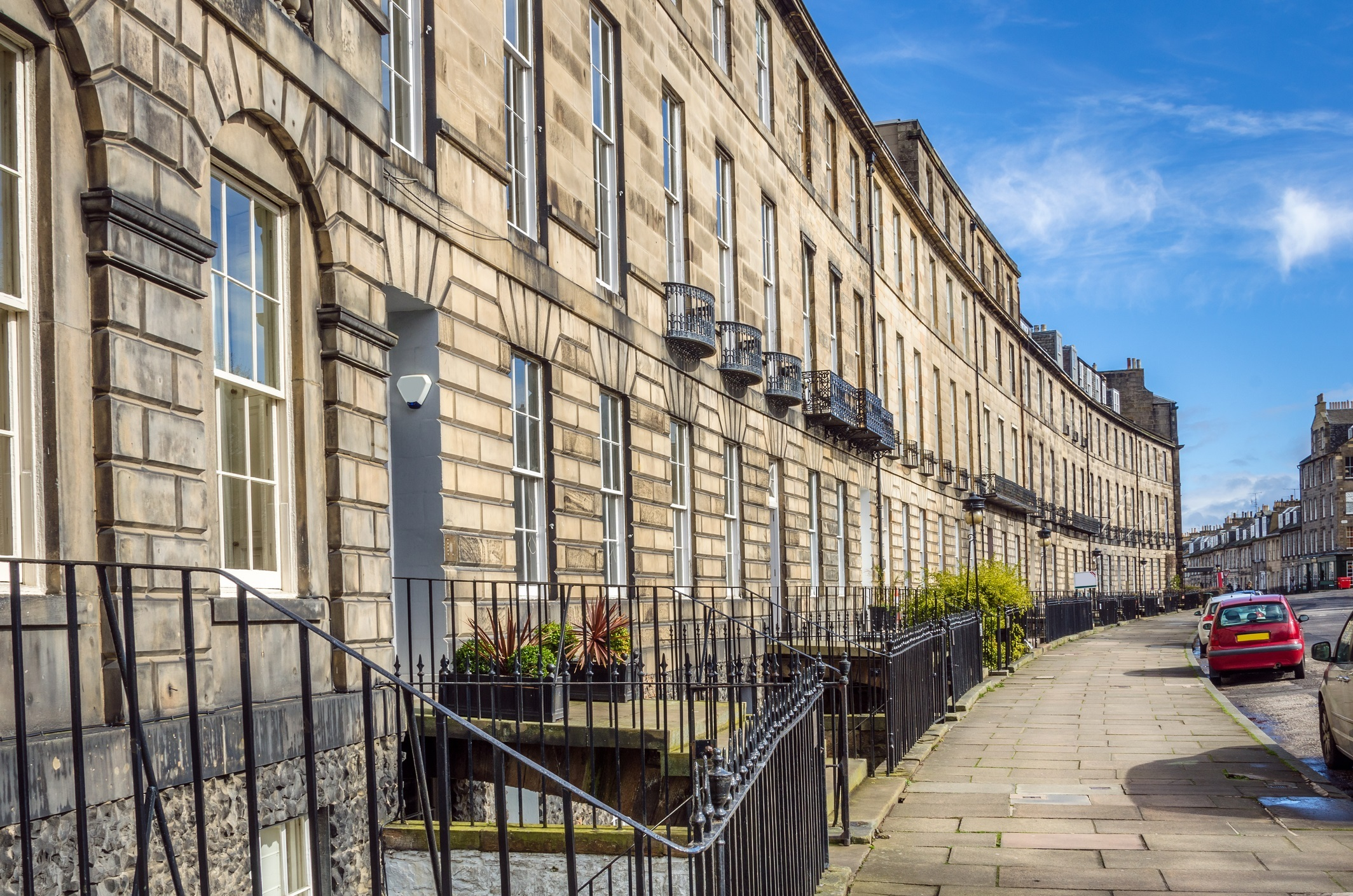 Town Houses in in the New Town of Edinburgh on a Clear Winter Day. The Traditional Stone Buildings line a curving cobbled pavement..