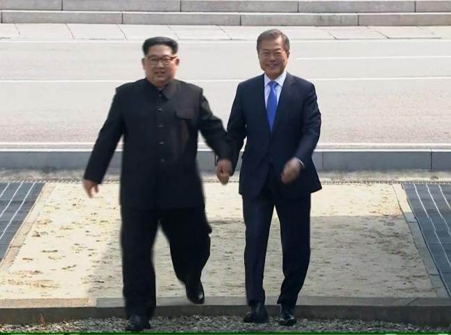 North Korean leader Kim Jong Un, left, crosses the border into South Korea, along with South Korean President Moon Jae-in for historic face-to-face talks at the end of last month. Kim's move to synchronise time zones is a symbolic part of the reconcil