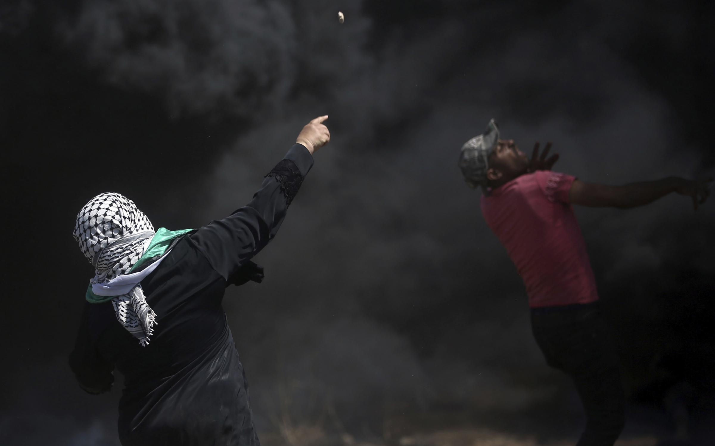 Palestinian protesters hurl stones at Israeli troops during a protest at the Gaza border. Picture: AP Khalil Hamra