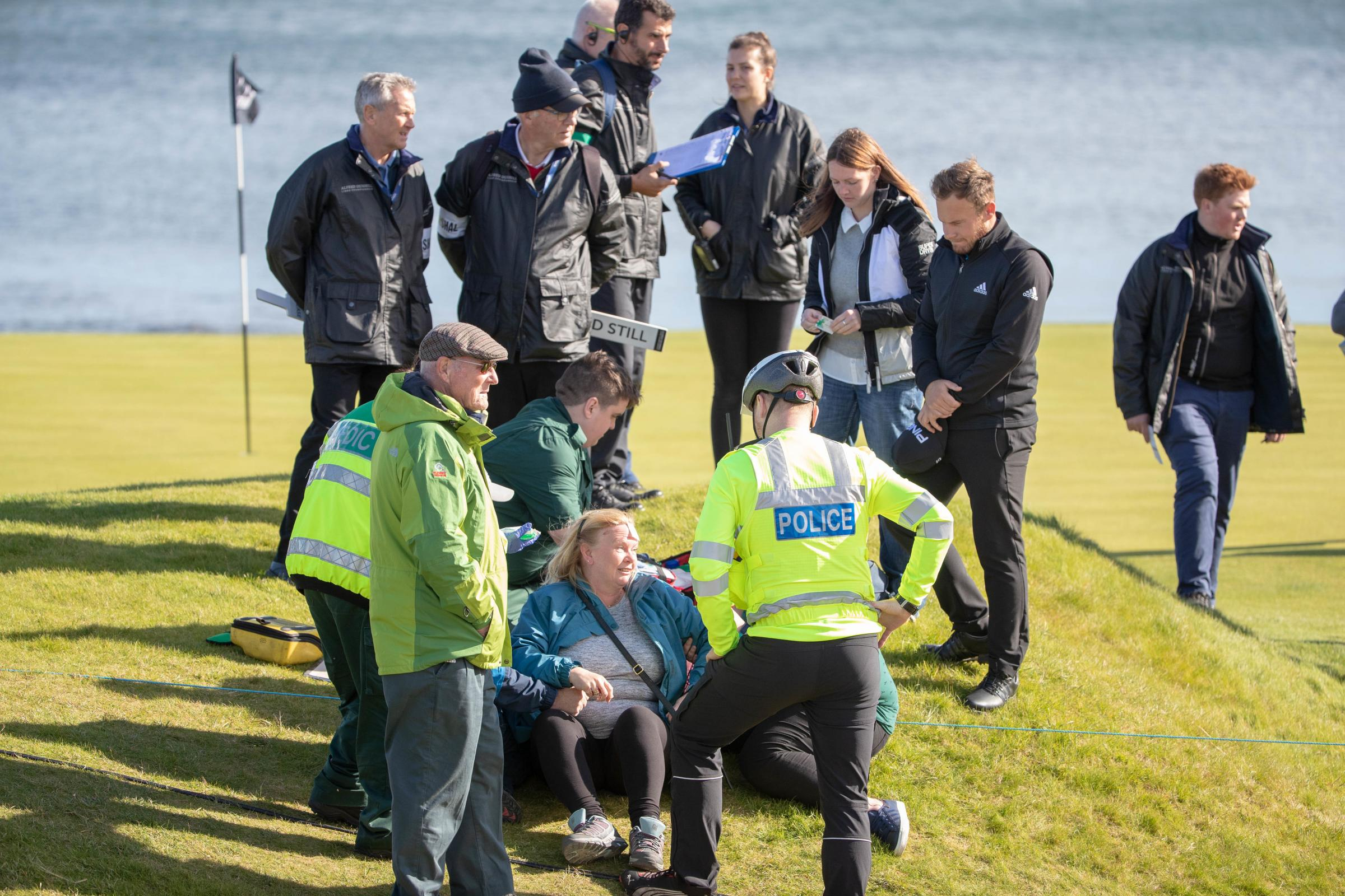 England's Tyrell Hatton stands over a spectator who he hit with his tee shot at the15th hole, prior to being taken back to the medical centre during day one at Kingsbarns Golf Course, St Andrews PRESS ASSOCIATION Photo. Picture date: T