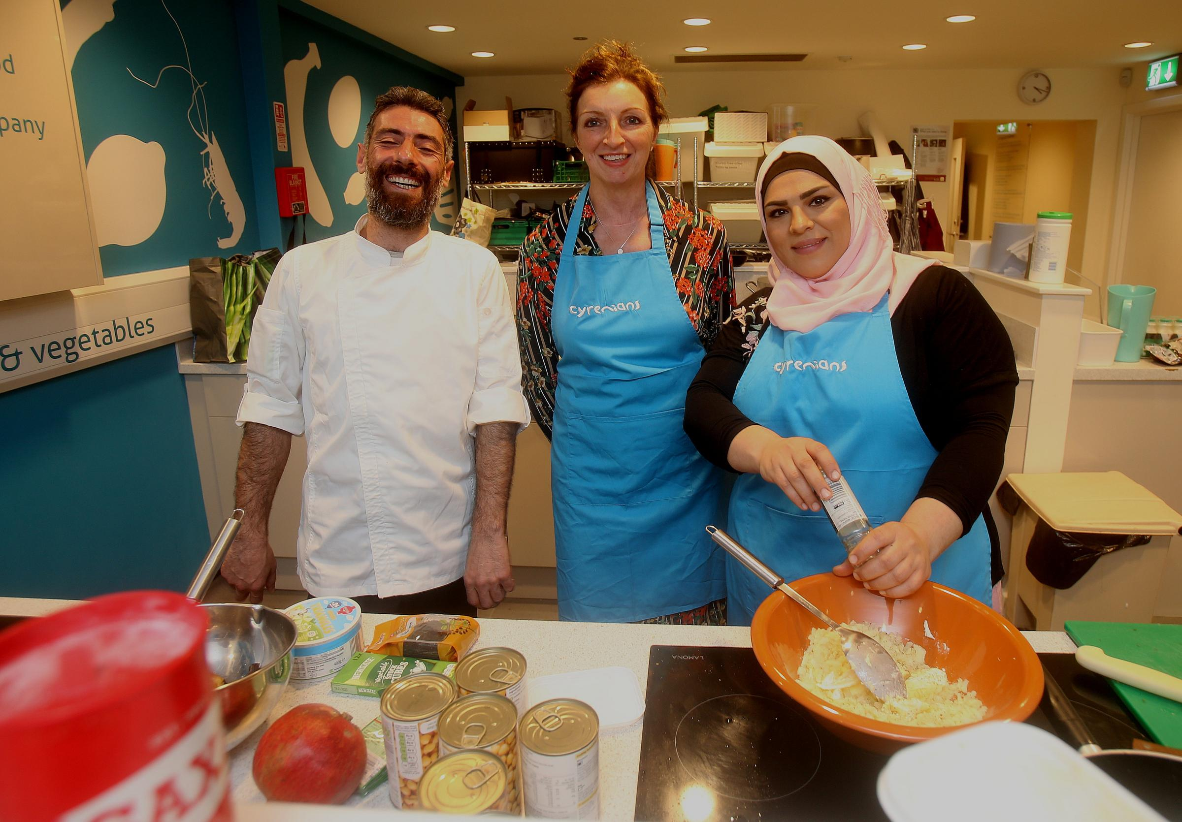 Chefs and Syrian refugees Noura Selibi, right, and Ryad Youssef with organiser Pam Timms, centre, at the Syrian Supper Club in Leith Cyrenians. STY DEVINE