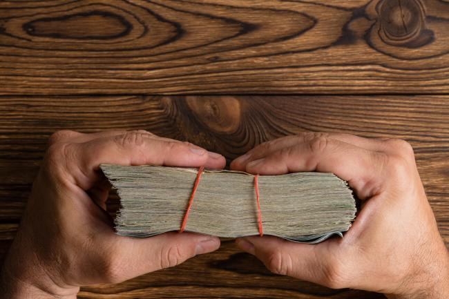 Male hands holding a thick wad of money tied with rubber bands over a rustic wood table viewed edge on from above with copy space.