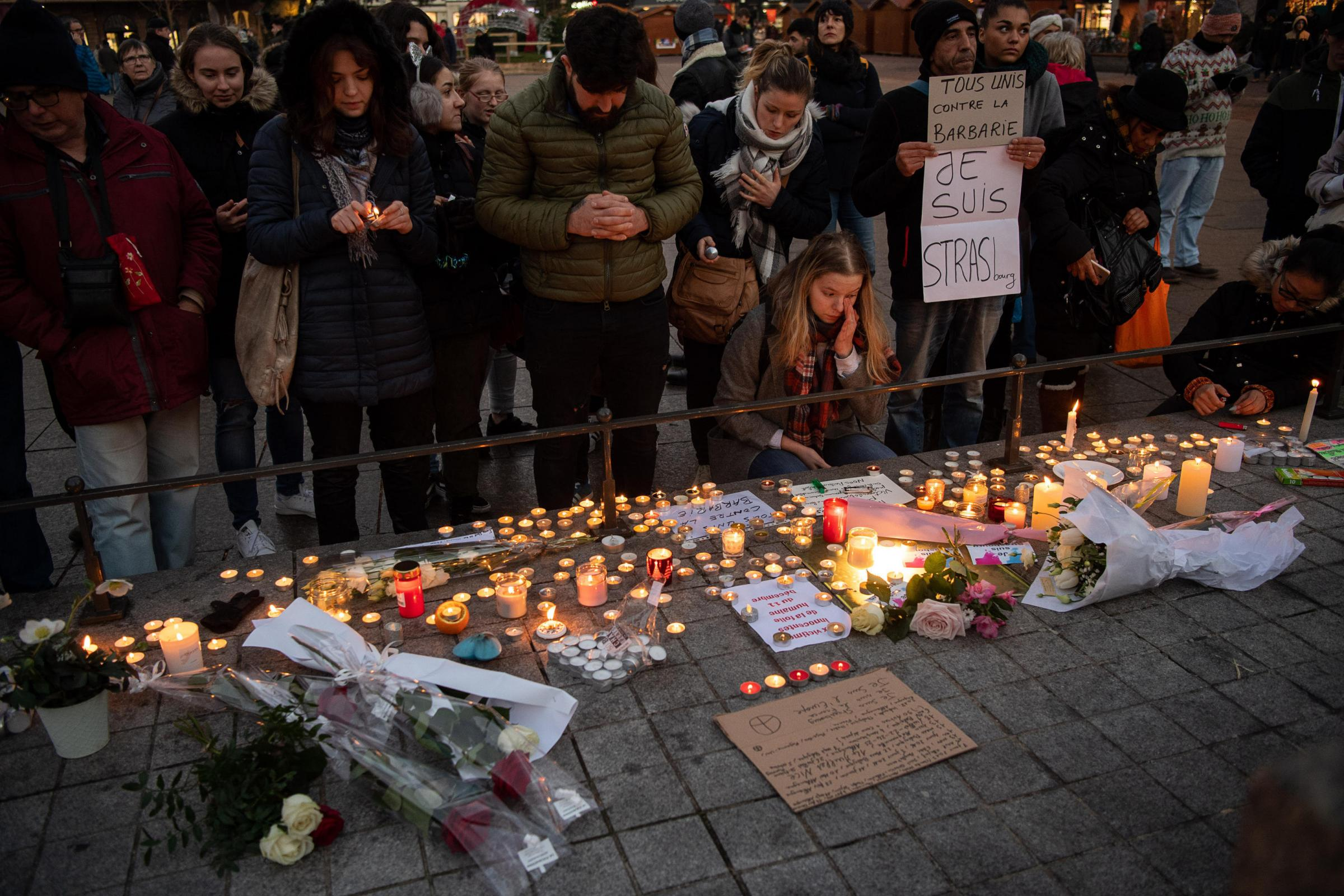 Alamy Live News. R833JW Strasbourg, France. 12 December 2018, France (France), StraBburg: Mourners stand near the Strasbourg Christmas market behind numerous burning candles. The investigators assume that the deadly attack last night was a terrorist attac