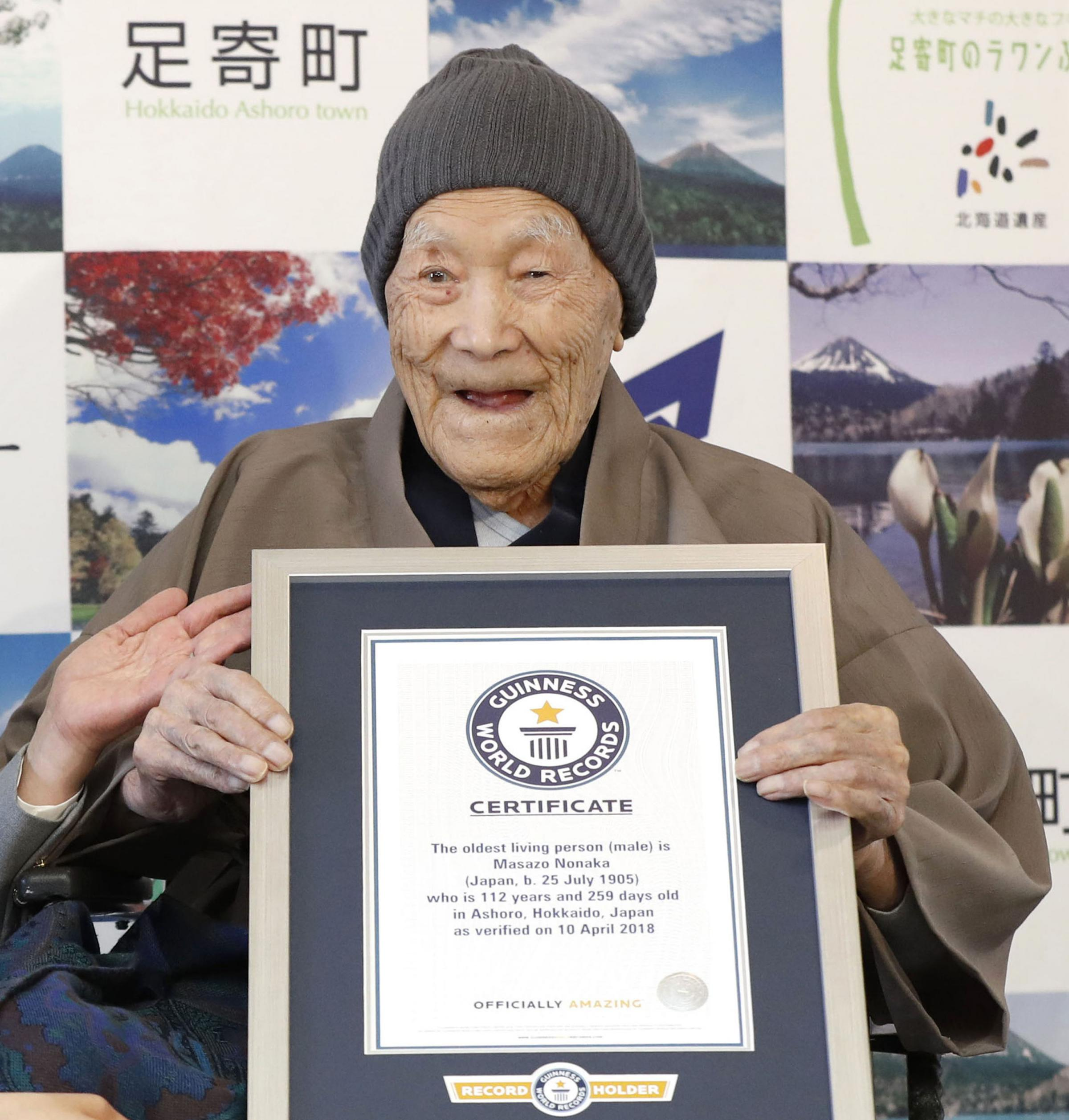 In this April 10, 2018, file photo, Masazo Nonaka eats a cake after receiving the certificate from Guinness World Records as the world's oldest living man at then age 112 years and 259 days during a ceremony in Ashoro on Japan's northern main isl