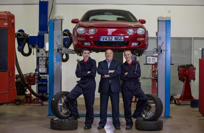 Jim McColl (centre) with  Newlands Junior College pupils Eden Harley 15 from Govanhill (left) and Conor Payling 15 from Holytown (right) at the GTC Training Centre in Glasgow..It is to promoting the new Proj-X programme where  they repair and restore a ca