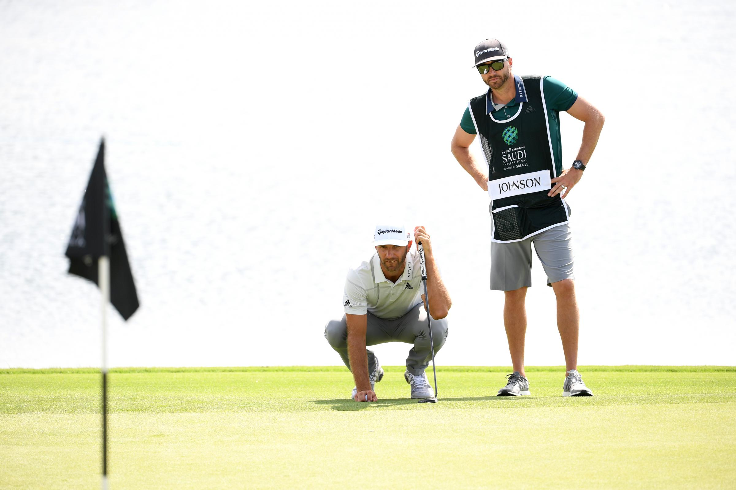 Dustin Johnson and his caddie and brother Austin Johnson line up a putt on the ninth hole during Day two of the Saudi International