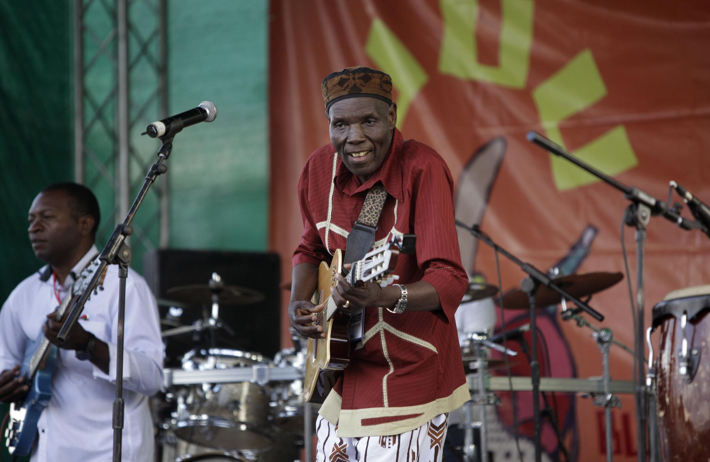 FILE - In this Sunday, Nov. 6, 2011 file photo, Zimbabwean music superstar and U.N. goodwill ambassador Oliver Mtukudzi, center, performs at a music festival held in Karen on the outskirts of Nairobi, Kenya. Zimbabwean musician and world music star Oliver