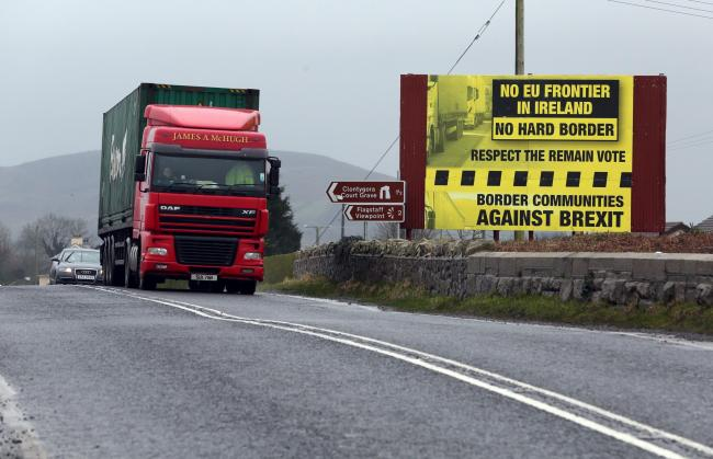 Traffic passing a protest sign on the border between Ireland and Northern Ireland.