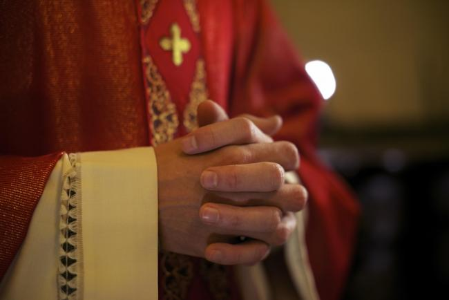 Catholic priest on altar praying with hands joined during mass service in church.