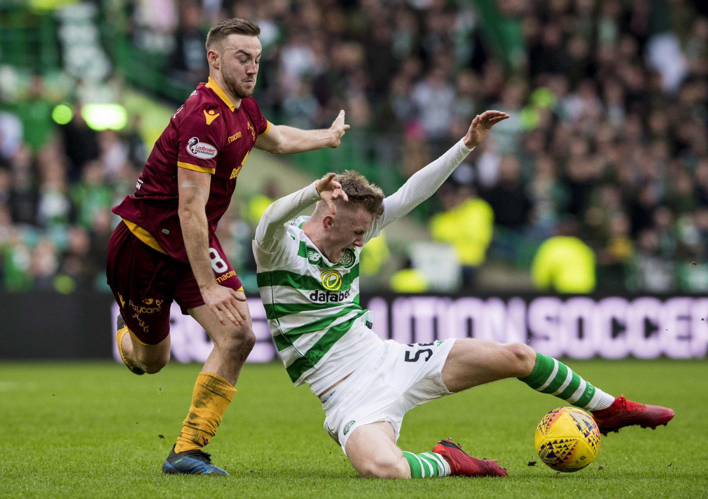 Ewan Henderson, man of the match in his first Celtic start, slides in on Motherwell's Allan Campbell