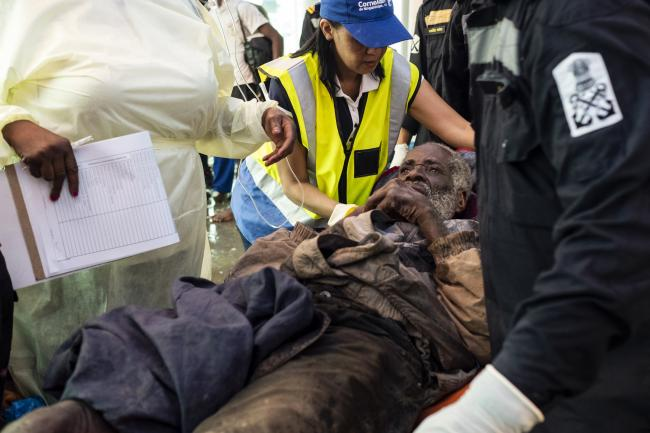 Francisco Romao Domingos, an elderly man, is carried on a stretcher to the medical and triage centre at the port of Beira.