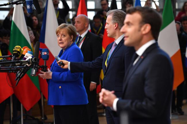Angela Merkel looks on as Emmanuel Macron addresses the media ahead of the European Council meeting in Brussels on Wednesday.