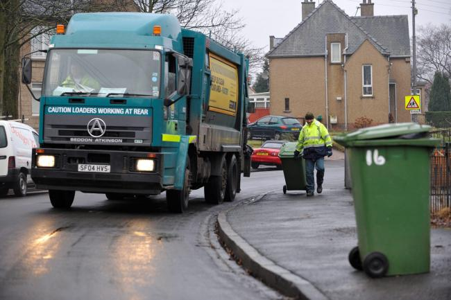 Glasgow City Council refuse collection now operating at the weekend..Refuse collectors  empty wheelie bins in Knightswood area.