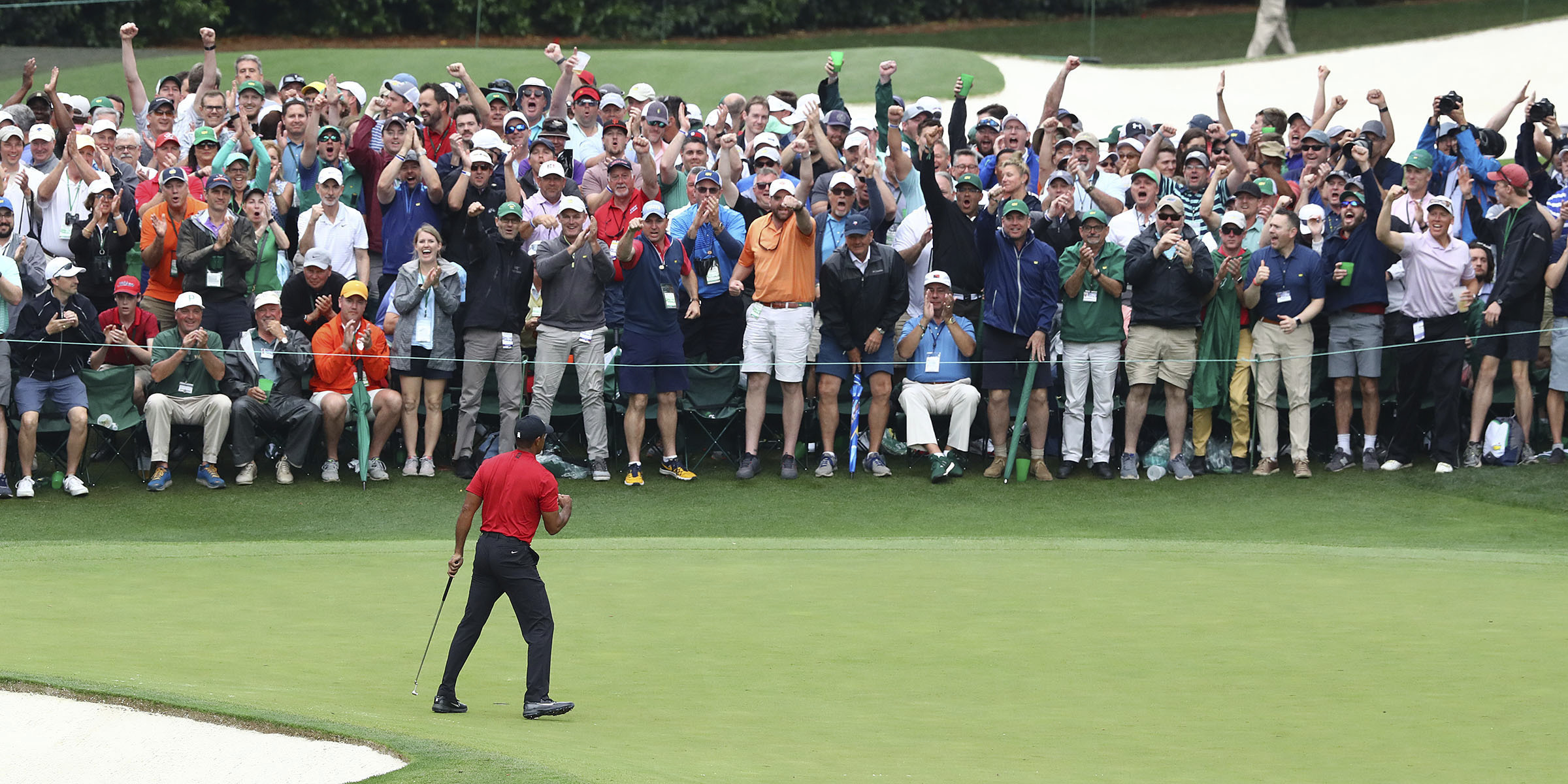 The gallery reacts as Tiger Woods makes his birdie putt on the 16th green on his way to winning the Masters by one stroke at Augusta National Golf Club on Sunday. Curtis Compton/ccompton@ajc.com