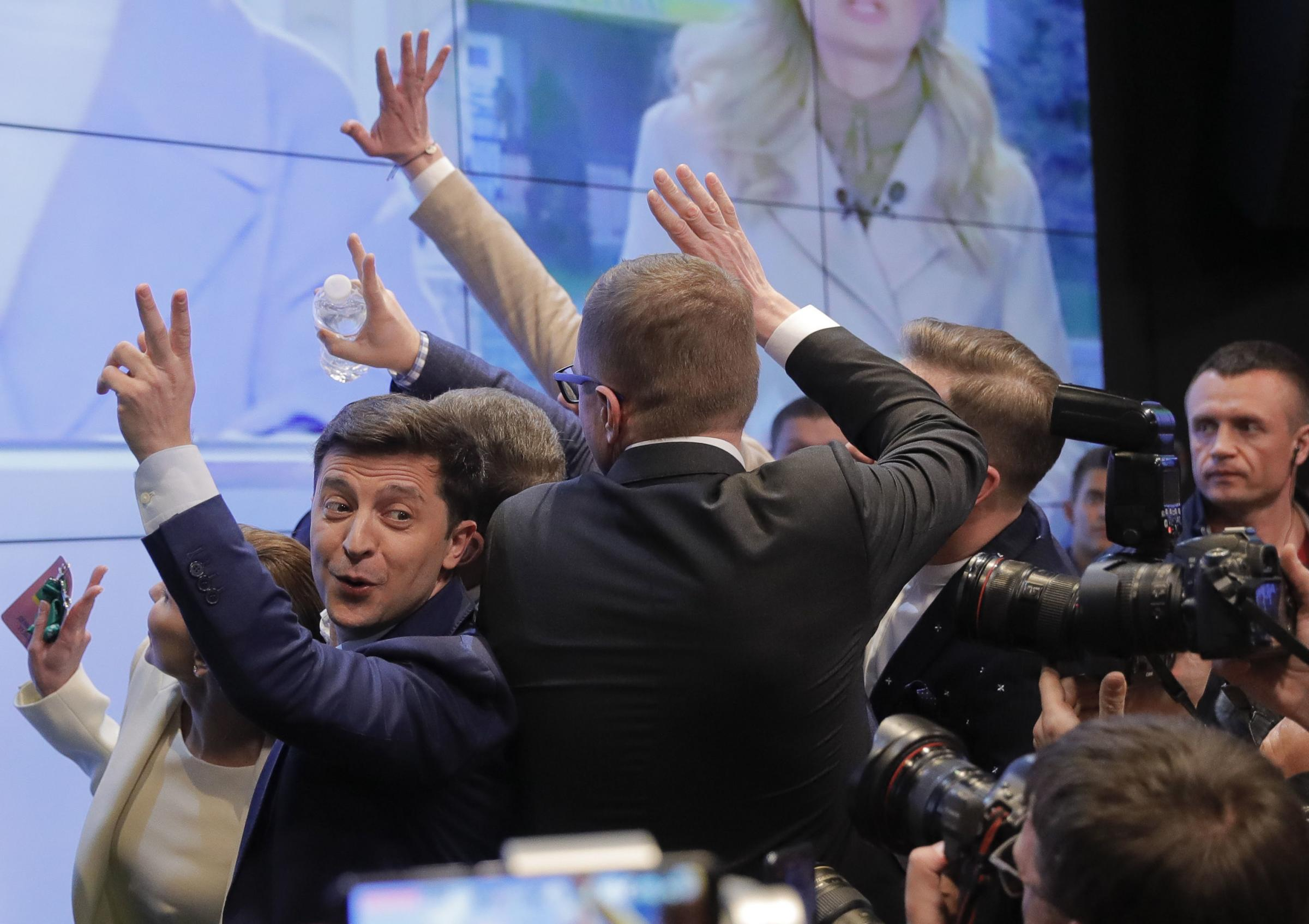 In this Sunday, April 21, 2019, photo, Ukrainian comedian and presidential candidate Volodymyr Zelenskiy, left, makes the victory sign after seeing the exit polls for the second round of presidential elections in Kiev, Ukraine. Ukrainians voted on Sunday