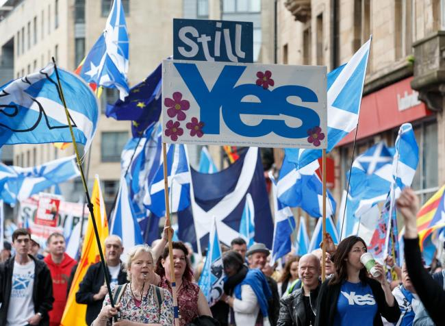 People taking part in the March for Independence wave Saltires as they process through Glasgow city centre