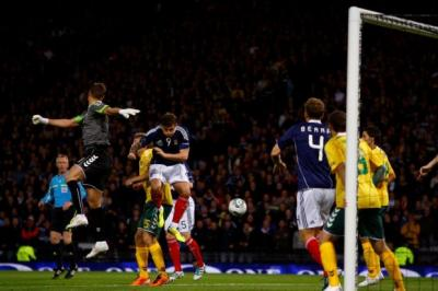 David Goodwillie beats the Lithuania goalkeeper to the ball but fails to convert. Picture: Martin Shields