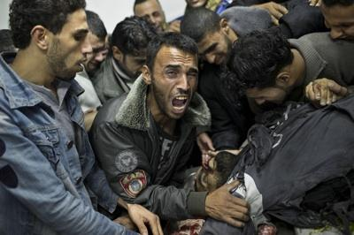 A Palestinian man cries next the body of a dead relative in the morgue of Shifa Hospital in Gaza City