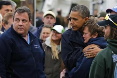 AFTERMATH: President Obama, top, and Governor Christie offer comfort to survivors in New Jersey, as a rollercoaster, left, lies buckled and stranded in the sea, and members of SUNY Maritime Academy use boats to help rescue victims. Main picture: Reuters