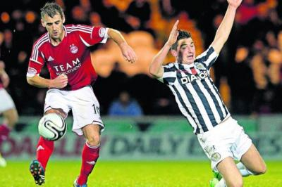 Aberdeen's Niall McGinn picks up the ball as Kenny McLean of St Mirren goes down Photograph: SNS