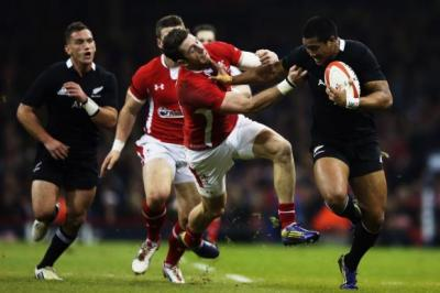 New Zealand's Julian Savea delivers a powerful hand-off to Wales' Alex Cuthbert                Photograph: Getty