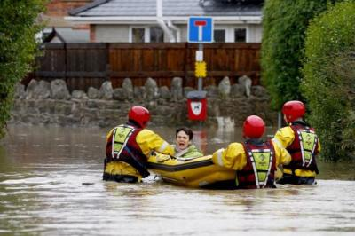 MESS: Residents wade through a street in St Asaph, Wales.