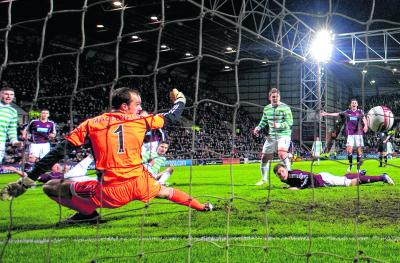 Jamie MacDonald can only watch as Mikael Lustig's shot heads for the net to put Celtic two goals in front