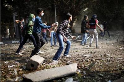 PROTESTS: Demonstrators, angry at President Mursi's new decree, throw stones during clashes with police in Cairo's Tahrir Square. Picture: Reuters