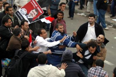 CONFRONTATION: Supporters of the Muslim Brotherhood attack an Egyptian opposition protester in front of the presidential palace. Picture: EPA