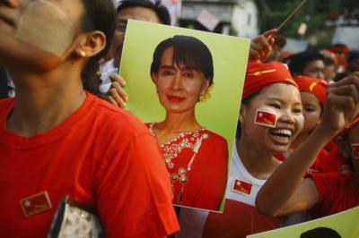 winning SMILES:Supporters of  Aung San Suu Kyi cheer her at her party headquarters in Yangon. Left, nuns celebrate Ms Suu Kyi's win. Main picture: Reuters
