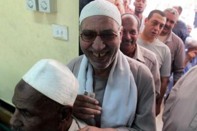jubilant: Egyptian men queue to vote in the first round of historic presidential  elections in Cairo. Left, a woman  shows her  ink-marked finger after casting her vote and an elderly woman is assisted outside a polling station in the capital.  Main picture:  EPA