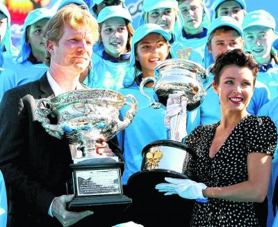 Jim Courier and Dannii Minogue get their hands on the trophies at Roland Garros. Picture: Getty Images
