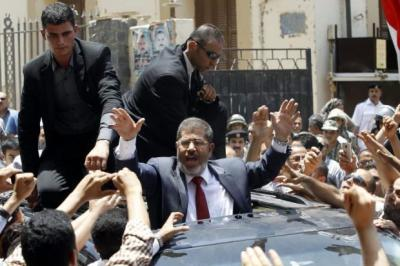 Above, Muslim Brotherhood candidate Mohamed Mursi casts his vote, as Egyptians return to the polls this weekend. Inset left, clashes in Cairo last year eventually led to some changes being made Photographs: AFP; Getty Images; Reuters
