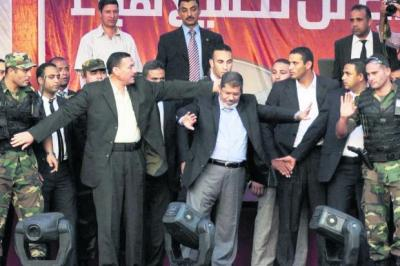 Mohammed Mursi gestures to his security guards to let him greet supporters in Cairo's iconic Tahrir Square