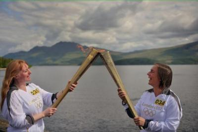 FIRED UP: Sheila McNeil passes the Olympic flame to Ruth Leith in Luss, above, and actor James McAvoy carries the torch, left Main picture: Getty Images FIRED UP: Shelia McNeil passes the Olympic flame to Ruth Leith in Luss earlier this month.