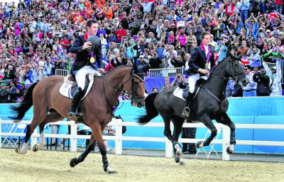 Scott Brash, left, takes Hello Sanctos on a victory lap after winning team gold. Picture: EPA