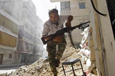 BATTLE HARDENED: A Free Syrian Army fighter takes cover during clashes with the Syrian army in the Salaheddine district of Aleppo.