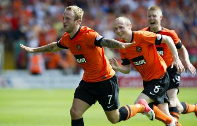 Johnny Russell is met by his team-mates as he celebrates scoring the second goal of a derby that his side dominated.