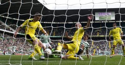 Mikael Lustig slides in to score his and Celtic's second goal. Picture: David Moir